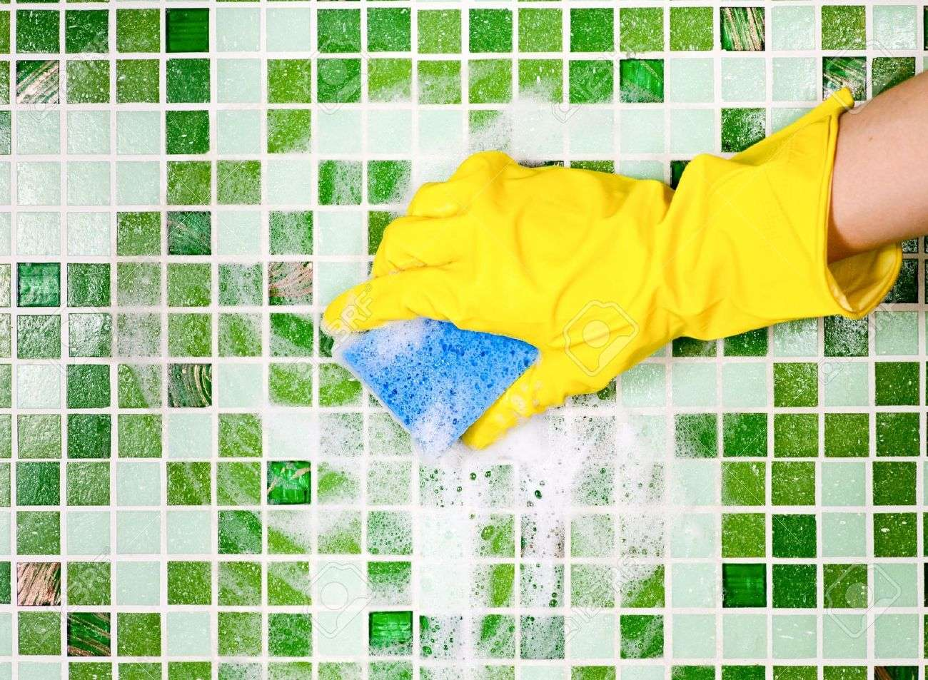 6559732-Hand-in-yellow-protective-glove-cleaning-mosaic-wall-Stock-Photo